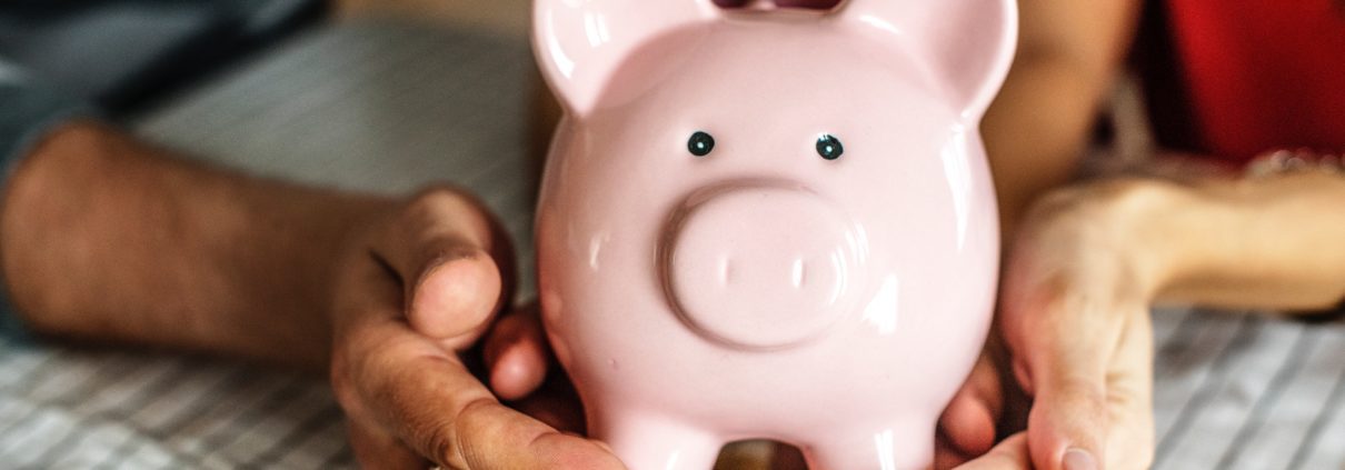A woman, man, and a kid holding a pink piggy bank