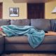 woman lying on the couch covering her body with a blue blanket